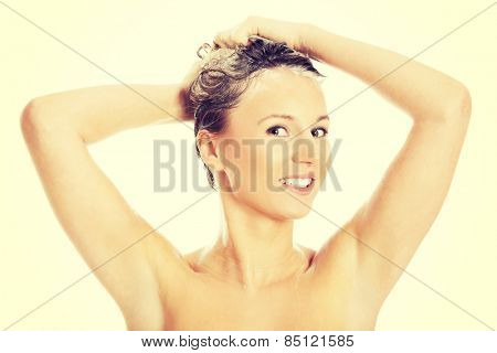 Woman taking a shower and shampooing her hair. poster