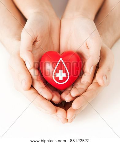 healthcare, medicine and blood donation concept - male and female hands holding red heart with donor sign