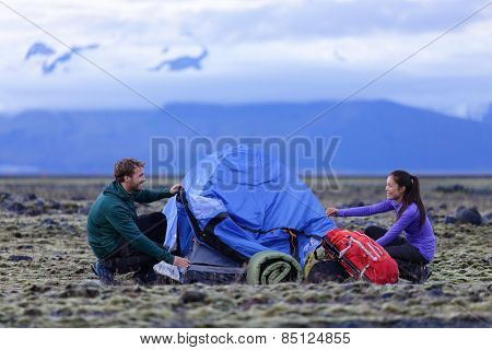 Tent - people pitching tent on Iceland at dusk. Couple setting up camp for night after hiking in the wild Icelandic nature landscape. Multicultural Asian woman and Caucasian man healthy lifestyle.
