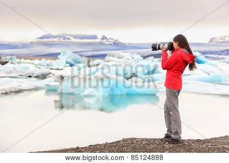 Nature landscape photographer taking picture photos with SLR camera on Iceland Jokulsarlon glacial lagoon / glacier lake. Woman taking photograph of beautiful Icelandic nature with Vatnajokull.