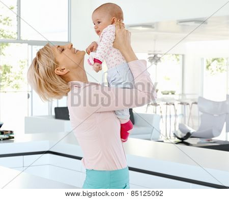 Happy casual blonde caucasian mother with cute baby at bright home indoors. Holding, raising, joy, family, smiling, standing.