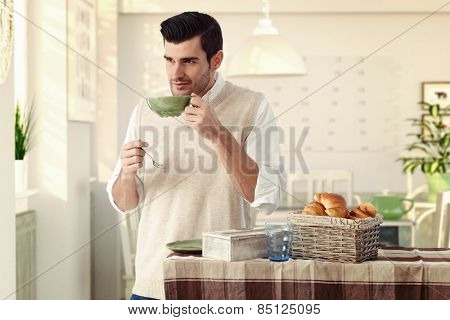 Handsome casual caucasian man drinking morning breakfast tea at vintage home with tea cup and spoon in hand. Wearing sleeveless sweater, standing at dining room, wondering, thinking, smiling, bristly.