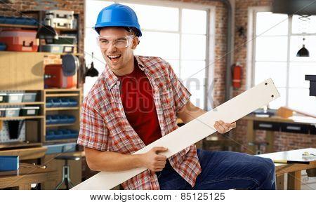 Happy casual caucasian man in hardhat having fun at DIY workshop. Smiling, standing, air guitar.