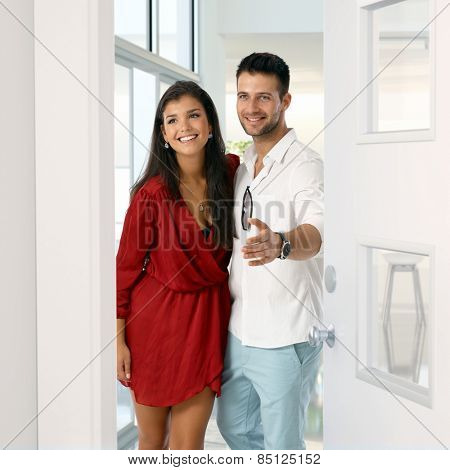 Happy young attractive caucasian couple standing in new home doorway. Smiling, standing, gesturing, home finance.