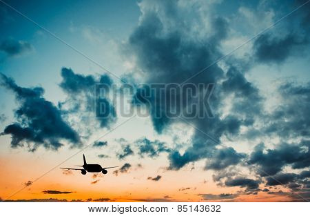 Airplane in the sky at sunset