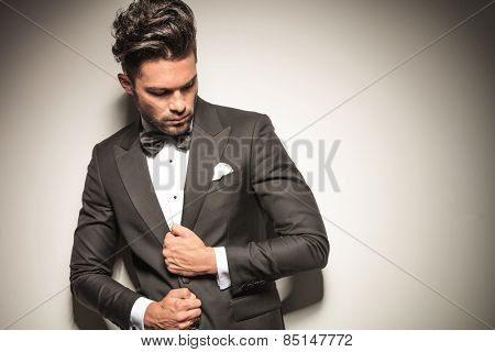 Elegant business man looking down while fixing his jacket. poster