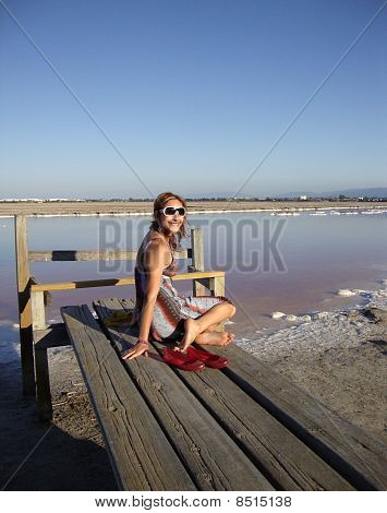 Attractive 20-something Lady Sits On A Pier In Front Of Purple Salt Mashes