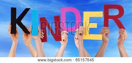 People Holding Colorful Word Kinder Means Kids Blue Sky