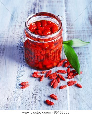 Goji berries in glass bottle with leaves on color wooden table background