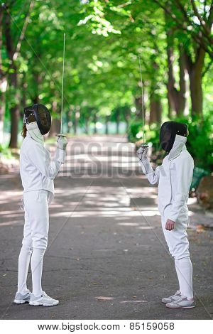 Two rapier fencers women staying in park alley getting ready for competition