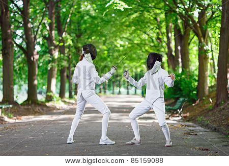 Two rapier fencers women staying in park alley getting ready for competition poster