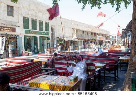 DOHA, QATAR - MARCH 8, 2015:  A traditional street cafe in Souq Waqif with shoppers passing by and Qatari flags flying.