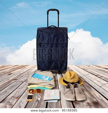 summer vacation, tourism and objects concept - travel bag, map, air ticket and clothes with personal stuff over wooden floor and blue sky background