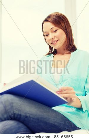 leasure and home concept - smiling woman reading book and sitting on couch at home