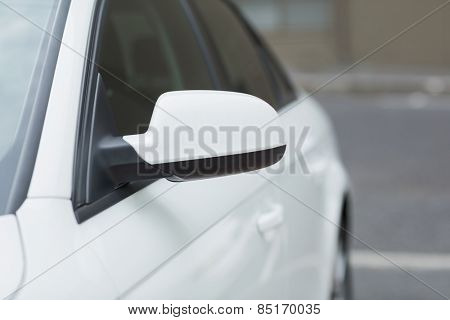 Close up of a wing mirror of white car