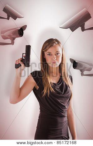 Femme fatale pointing gun up against cctv camera