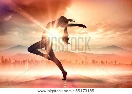 Side view of a sporty young woman stretching against sun shining over road and city