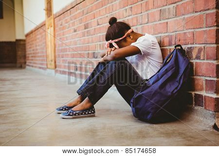 Full length of tensed girl sitting against brick wall in school corridor