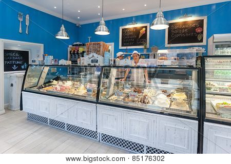 DUBROVNIK, CROATIA - MAY 26, 2014: Smiling young waitress at Gossip ice cream shop on main street Stradun. It is one of the best ice cream place in town popular among tourists.