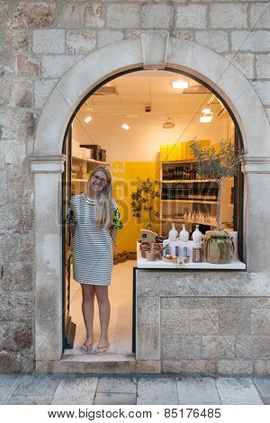 DUBROVNIK, CROATIA - MAY 28, 2014: Sales woman standing at  entrance to souvenir shop on Stradun, main street in Dubrovnik.