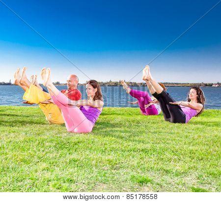 Young people practice Yoga asana on lakeside. Yoga concept.