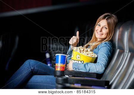 Side view portrait of happy woman showing thumbsup while holding snacks at cinema theater