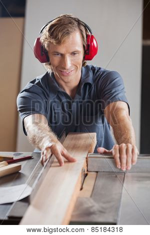 Mid adult carpenter using tablesaw to cut wooden plank in workshop