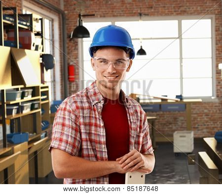 Happy rookie casual caucasian worker with hardhat at workshop. Smiling, standing, looking at camera, safety glasses.
