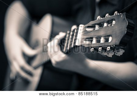Classic guitar - Vintage toned image of musician hands playing an acoustic guitar