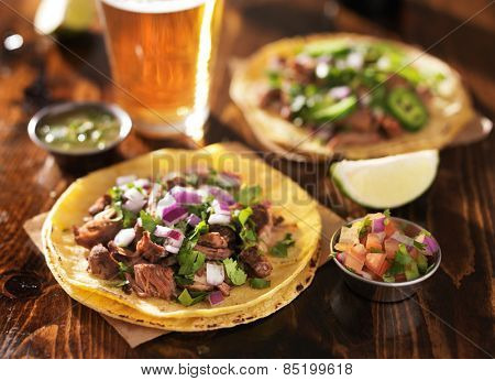 authentic mexican tacos with beer on wooden table shot with selective focus poster