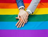 people, homosexuality, same-sex marriage, gay and love concept - close up of happy male gay couple hands over rainbow flag poster