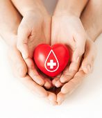 healthcare, medicine and blood donation concept - male and female hands holding red heart with donor sign poster