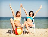 summer holidays and vacation - girls in bikinis sunbathing on the beach chairs poster