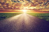 Long straight road, way towards sun. Sunset sky, travel, transport, destination concepts. poster