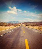 Vintage retro effect filtered hipster style image of travel forward concept background -  road in desert poster