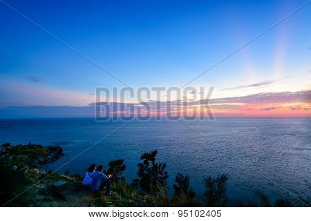 Couple And Tourists Waiting For The Sunset Over The Sea