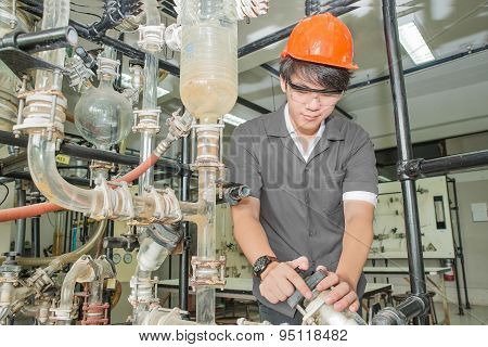 Asian engineer student turning pipeline pump for training in laboratory poster