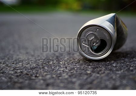 Crushed aluminum can discarded on side of road