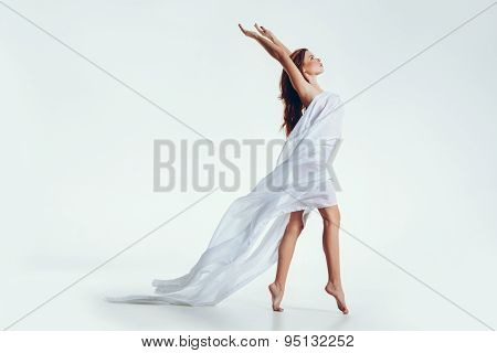 Side view portrait of a nude woman with hands raised in the studio. Attractive young woman with transparent fabric posing on white background. poster