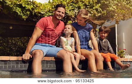 Beautiful Young Family Sitting Next To Swimming Pool