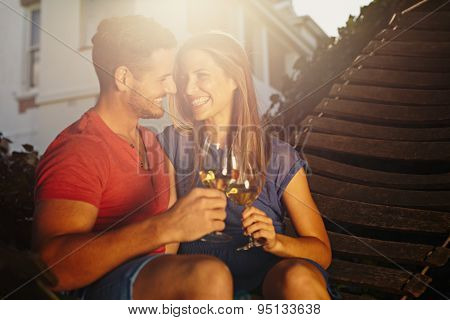 Couple Relaxing In Hammock Toasting Each Other With Wine