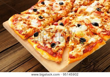 Al Funghi Pizza With Olives Cut In Sectors On Wooden Board
