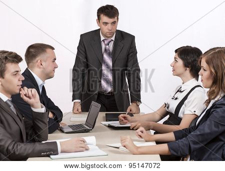 Severe corporate manager is observing his business team