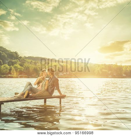 Couple in love sitting on the pier