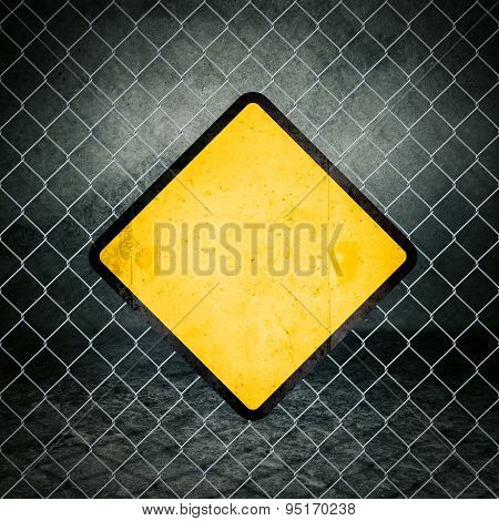 Grunge Yellow Warning Sign On Chainlink Fence Of Industrial Warehouse