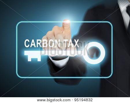 Male Hand Pressing Carbon Tax Key Button