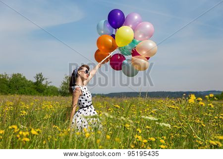 Young Woman With A Rockabilly Dot Dress And A Lot Of Balloons In The Meadow