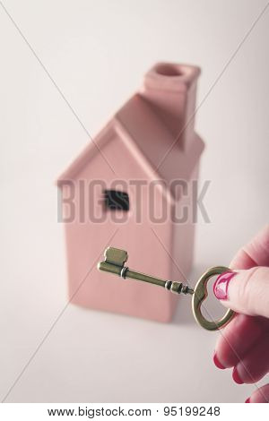 Toy Pink House With Hand Holding Key In Front