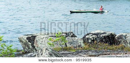 Rocky Coast Of Lake With A Small Pine.