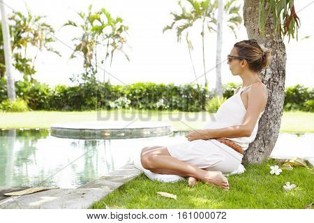 Expectant Mother Wearing Sunglasses Having Rest In Open Air, Sitting On Grass Under Tree, Enjoying S